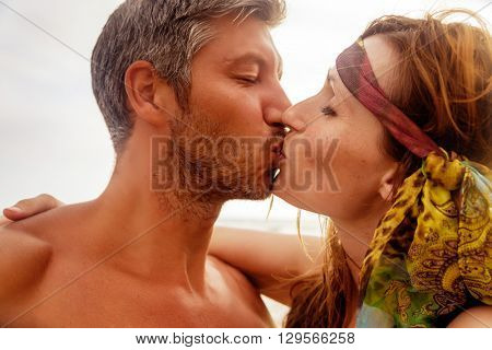 kissing younger sunset people on the beach