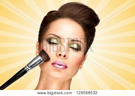Glamour girl with retro fashion hairstyle applying dry cosmetic tonal foundation on the face using makeup brush on colorful abstract cartoon style background.