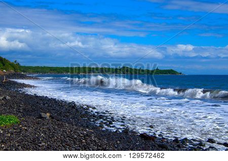 Tropical ocean waves breaking onto lava rock beach shoreline.  Scenic travel destination Maui, Hawaii.