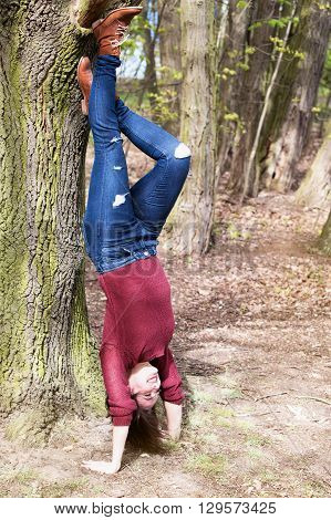 brunette woman making a headstand at a tree