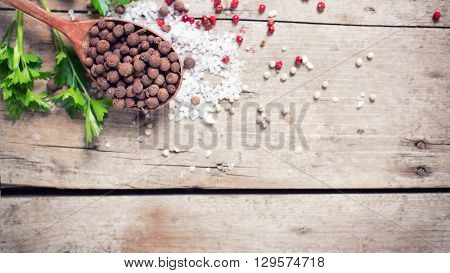 Seasoning for cooking. Allspice pepper in wooden spoon and sea salt red pepper and herb parsley on aged wooden background. Food ingredient. Selective focus. Place for text. Flat lay. Top view. Toned image.