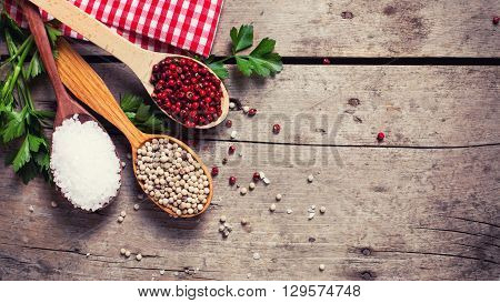 Seasoning for cooking. Red and white pepper and sea salt in wooden spoon on aged wooden background. Food ingredient. Selective focus. Place for text. Flat lay. Top view. Toned image.