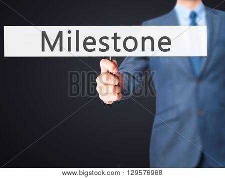 Milestone - Businessman Hand Holding Sign