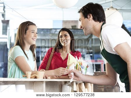 Girl Receiving Vanilla Ice Cream Cone From Waiter By Mother