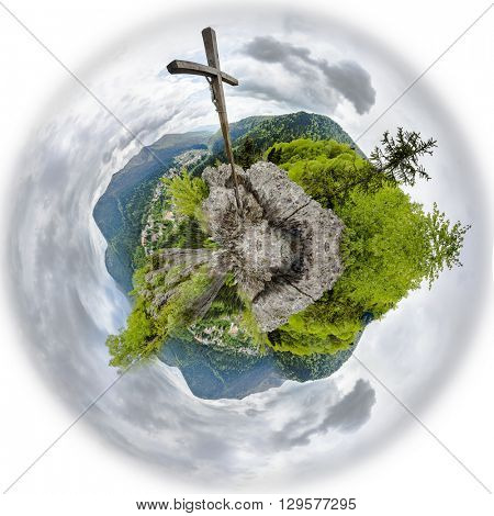 Large Christian wooden cross on a mountain peak of 360 degree miniplanet. Panoramic montage from 16 HDR images