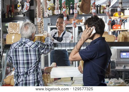 Saleswoman Selling Cheese To Customer At Shop