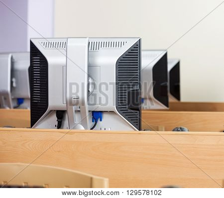 Computer Monitors Arranged In Row At Classroom