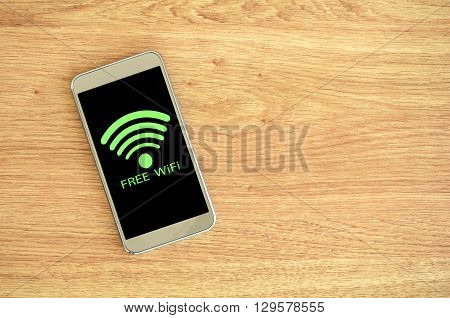 Free Wifi Available. Smart phone on wood background with free Wifi sign.