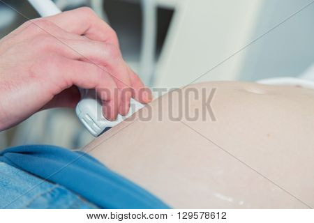 Pregnant woman getting ultrasound from doctor in clinic