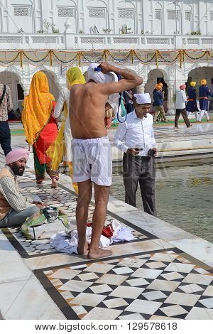 AMRITSAR INDIA - 30 OCTOBER 2015: People bathing in the lake at Golden Temple (Harmandir Sahib) in Amritsar Punjab India the holiest Sikh gurdwara in the world.