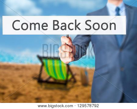 Come Back Soon - Businessman Hand Holding Sign