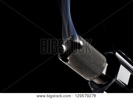 Smoke rising form the barrel of a firearm with a black background