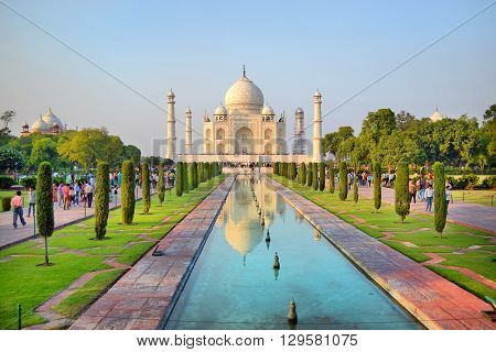 AGRA INDIA - 31 OCTOBER 2015: Tourists at the Taj Mahal. The temple is reflected in the pond.
