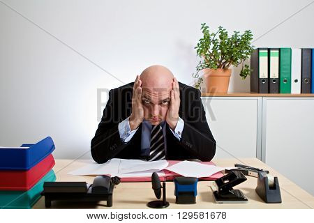 totally stressed manager. He holds his head with both hands