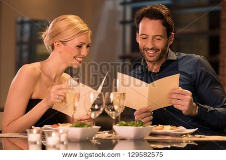 Happy young couple deciding on a dessert from menu card. Smiling couple with menus at luxury restaurant. Laughing and fun couple sitting at the restaurant table and reading a menu.