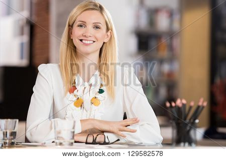Happy young business woman sitting at the desk. Beautiful blonde businesswoman smiling and looking at camera. Portrait of attractive designer smiling at camera in office. Happy secretary at desk.
