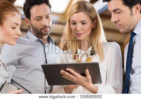 Business people in the office and looking at a digital tablet. Businesswoman holding tablet and sharing information with colleagues. Four business people collaborate and working together on tablet.