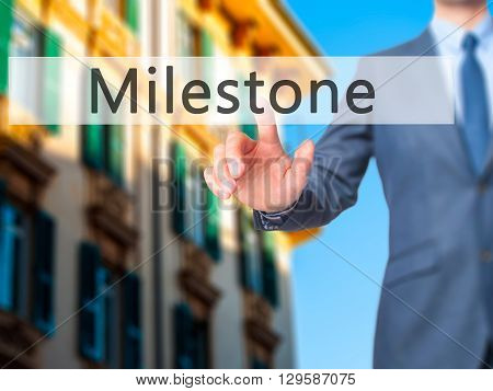 Milestone - Businessman Hand Pressing Button On Touch Screen Interface.
