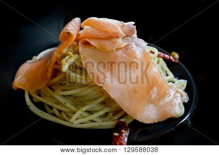Closeup Smoked salmon and spicy pasta in black plate
