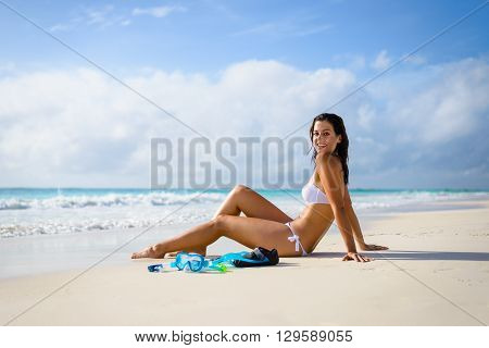 Relaxed beautiful young woman sunbathing on white sand towards tropical sea. Brunette tanned happy model enjoying summer tropical vacation and snorkel at seashore.