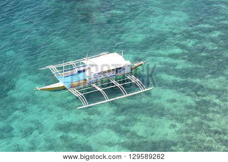 BOHOL PHILIPPINES - APRIL 5 2016: Outrigger anchored in the blue-green tropical waters off the coast of Bohol in the Philippines.
