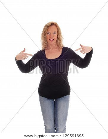 A blond middle age woman in jeans an black sweater pointing with her fingers at herself isolated for white background.