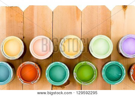 Pots Of Colorful Wood Stain On A Fence