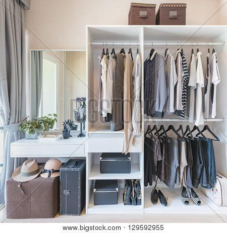 White Wardobe And Dressing Table With Clothes Hanging