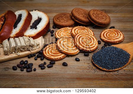 There are Pieces of Roll with Poppyseed,Cookies with Halavah,Chocolate Peas,Tasty Sweet  Food on the Wooden Background