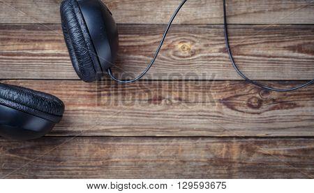 Headphones over wooden table.