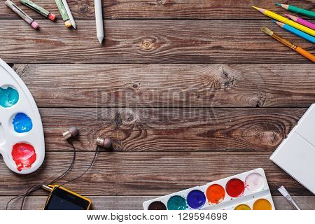 Paper, watercolors, paint brush and some art stuff on wooden   table