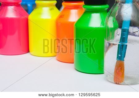 Paint brush in water in front of brightly coloured childrens paint pots for a rainy day activity