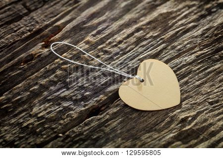 Close-up of carton heart shaped label with rope on wooden table