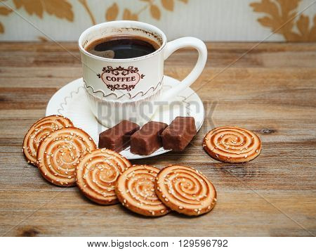 There are CookiesбChocolate Candy Porcelain Saucer and Cap with CoffeбTasty Sweet Food on the Wooden Background