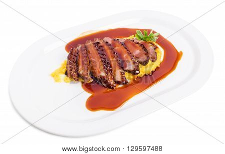 Delicious grilled duck breast on mango puree covered with red sauce. Isolated on a white background.