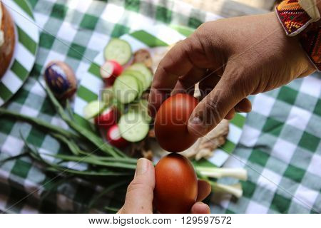 Two hands holding Easter painted eggs. Traditional Easter egg crack game. Male and female hands holding eggs. Eggs held by men with Easter table background.