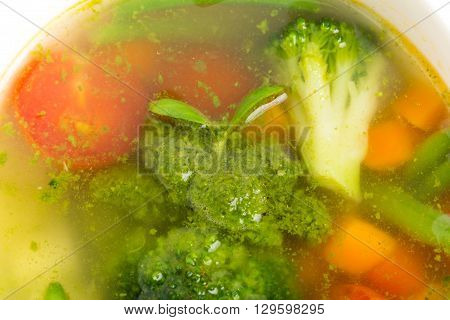 Bowl of minestrone soup with pesto. Focus on broccoli. Macro. Photo can be used as a whole background.