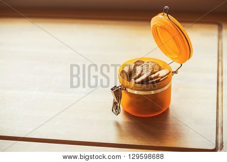 pretzels in jar with effect colors on wood background