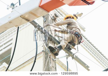 Close up of worker fixing power cord on the pole.