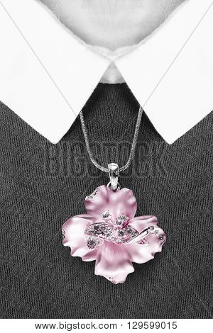 Pink flower pendant on black pullover with white collar closeup
