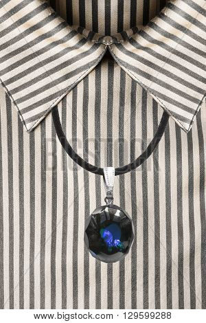 Blue crystal pendant on silk striped blouse closeup