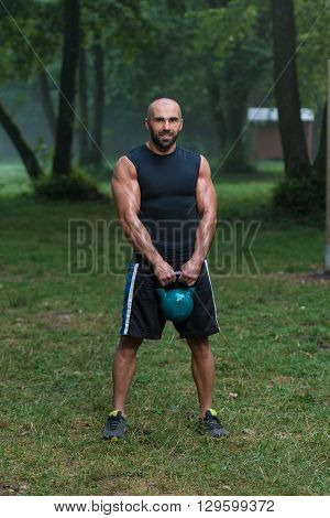 Attractive Male Athlete Performing A Kettle-bell Swing