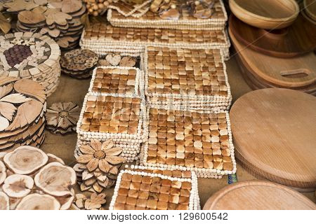 Handmade wooden vintage kitchen utensils for sale at the market. Various wooden kitchen tools. Different wooden tableware. Wooden stand under the hot pan.