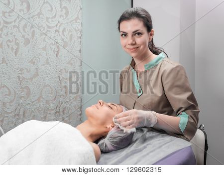 Beautician and the client before Facial Mask in beauty salon. Master beautician before the procedure Facial Mask in beauty salon. Cosmetician applying facial beauty mask for young woman at spa salon.