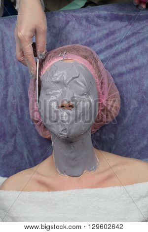 Girl doing lifting with Alginate Peel-Off Powder facial Mask in Beauty salon. Cosmetic Mask. Beautiful Young Woman Getting a Beauty Treatment in Spa Salon. Peeling, Beauty and body skin care.