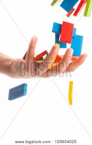 Falling colorful domino onto a hand on white
