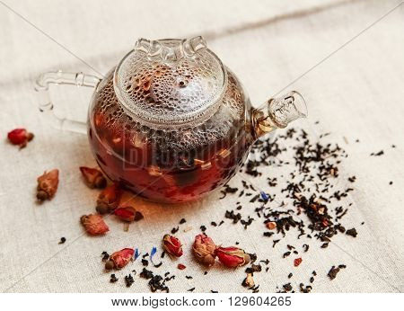 The Dry Red Small Roses with Black Tea in the Glass Teapot,Tea Drinking,Aromatized Flowers Rough Linen Tablecloth;Toned,Top View