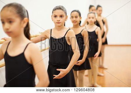 Portrait of a group of little girls paying attention to their teacher during class in a dance school