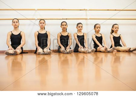 Group of pretty girls in leotards and skirts sitting and waiting for their dance class to begin