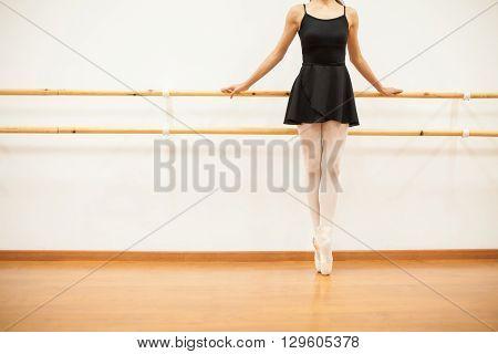 Ballet Dancer Tip Toeing Next To A Barre